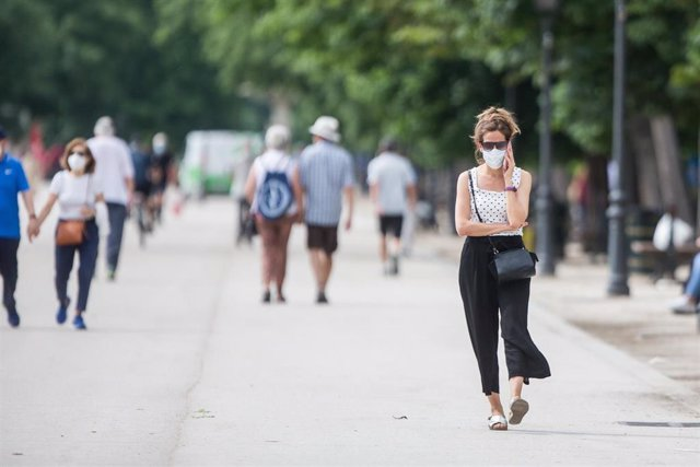 Varias personas pasean protegidas con mascarillas después de la reapertura del Parque de El Retiro.