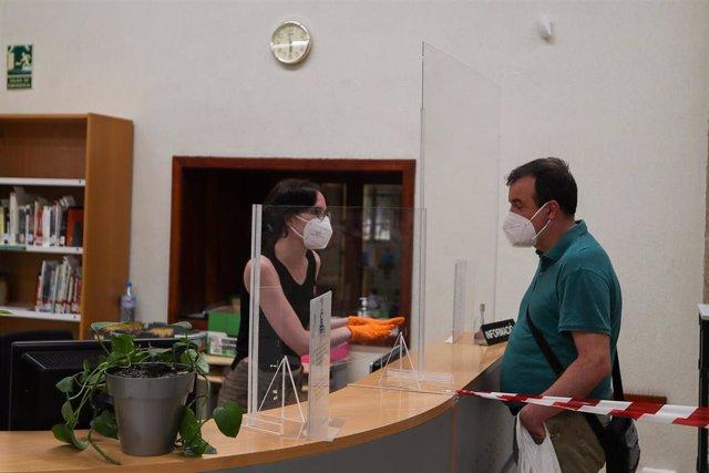Una trabajadora, protegida y con una mampara, atiende a una usuaria de la biblioteca municipal de Valencia abierta hace un mes tras el parón por el coronavirus, pero en la que sólo desde esta semana, al entrar la Comunidad Valenciana en la fase 3