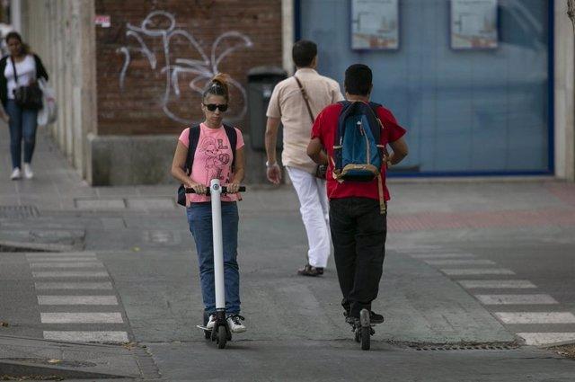Personas circulando por el carril bici en patinete eléctrico.