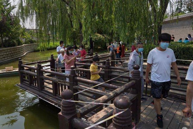 Varias personas con mascarilla por el coronavirus en Pekín.
