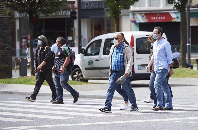 Transeúntes pasean por calles de Santander