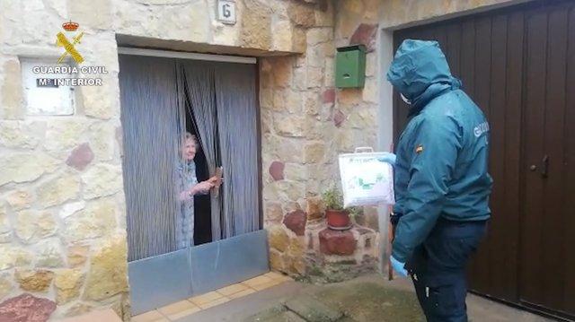 Un guardia civil entregando medicinas a una mujer mayor residente en un pueblo
