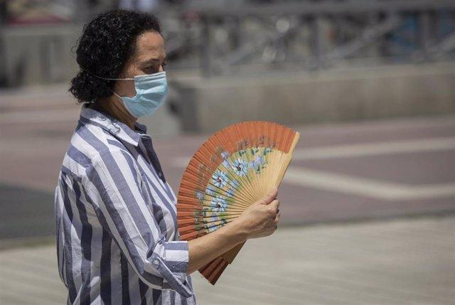 Una mujer con mascarilla se abanica mientras camina por Sevilla en un día de mayo con altas temperaturas