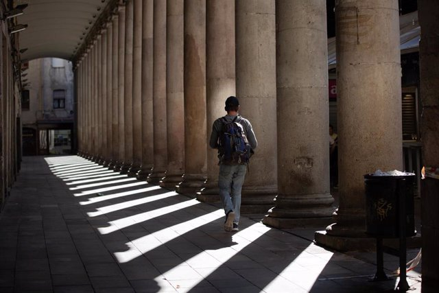 Un hombre camina por una calle de Barcelona.