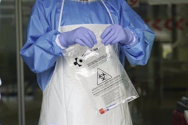 Un sanitario protegido con guantes sostiene una bolsa en la que hay una muestra para realizar un Análisis PCR.