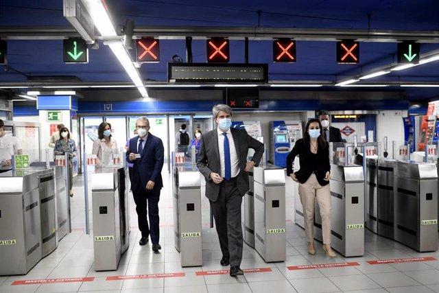 El consejero de Transportes, Ángel Garrido (c); y el presidente de Plena Inclusión, Mariano Casado (a su derecha), pasan por tornos de Metro durante la presentación de las nuevas medidas para facilitar la autonomía de personas con discapacidad intelectual