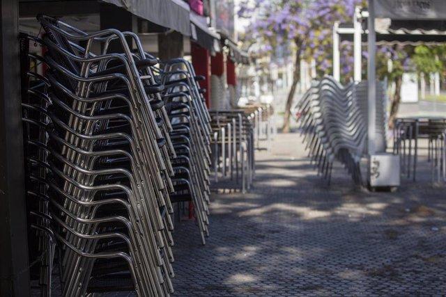 Sillas apiladas en la terraza de un bar, dos día después de que el Gobierno central presentara su plan de desescalada en la crisis del coronavirus. En Sevilla (Andalucía, España), a 30 de abril de 2020.