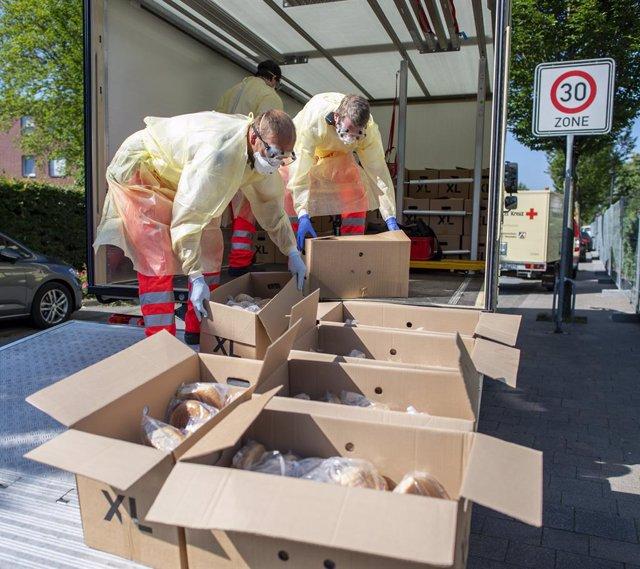 Voluntarios de la Cruz Roja reparten pan en varios bloques de apartamentos en los que viven trabajadores del grupo Toennies en cuarentena
