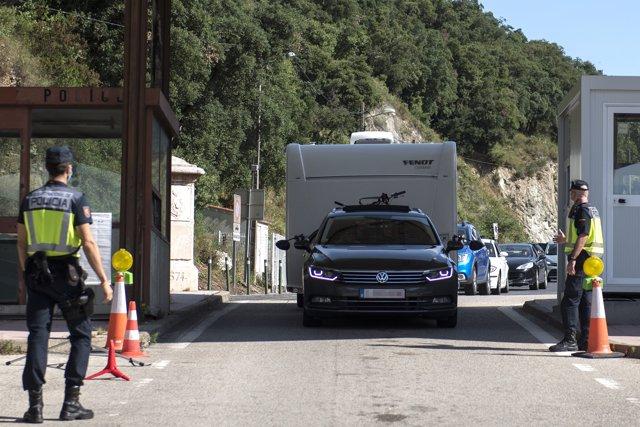 Dos agentes de la Policía Nacional controlan la frontera de La Junquera después de su reapertura tras la finalización del estado de alarma en España, a 21 de junio de 2020
