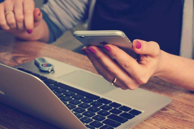 Una mujer mira su móvil mientras trabaja con su ordenador