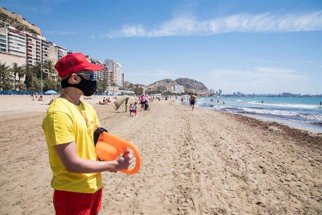 Un socorrista protegido con mascarilla vigila la Playa del Postiguet durante el primer día de la Fase 2, cuando se puede acceder a las playas de la misma provincia, isla o unidad territorial de referencia establecida en el plan de desescalada, y cuando lo