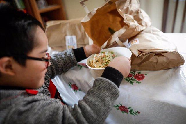 Un niño durante la comida en su casa del barrio madrileño de Carabanchel abre la tapa de un plato del menú de la ONG del chef José Andrés, a 14 de abril de 2020.