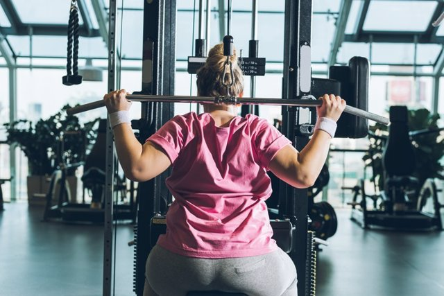 Mujer con sobrepeso haciendo deporte, gimnasio, pesas.