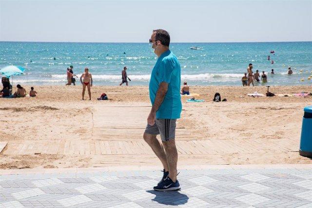 Un hombre protegido con mascarilla pasea por el paseo marítimo junto a la Playa del Postiguet durante el primer día de la Fase 2, cuando se puede acceder a las playas de la misma provincia, isla o unidad territorial de referencia establecida en el plan de
