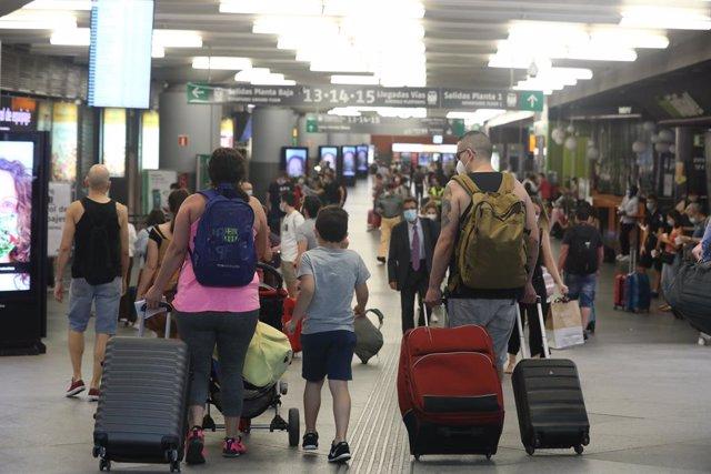 Una multitud de personas con maletas caminan por la estación de Renfe Madrid Puerta de Atocha en el primer día laborable tras el estado de alarma, en Madrid (España), a 22 de junio de 2020.