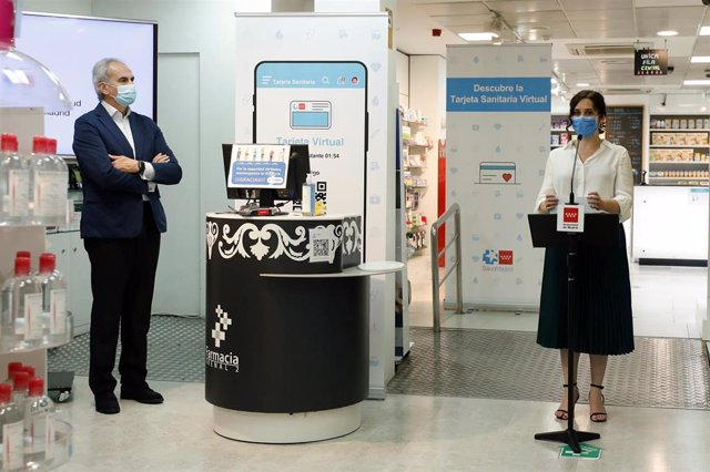 La presidenta de la Comunidad de Madrid, Isabel Díaz Ayuso presenta la Tarjeta Sanitaria Virtual, acompañada por el consejero de Sanidad del Gobierno regional, Enrique Ruiz Escudero, en una farmacia madrileña, en Madrid (España) a 22 de junio de 2020.