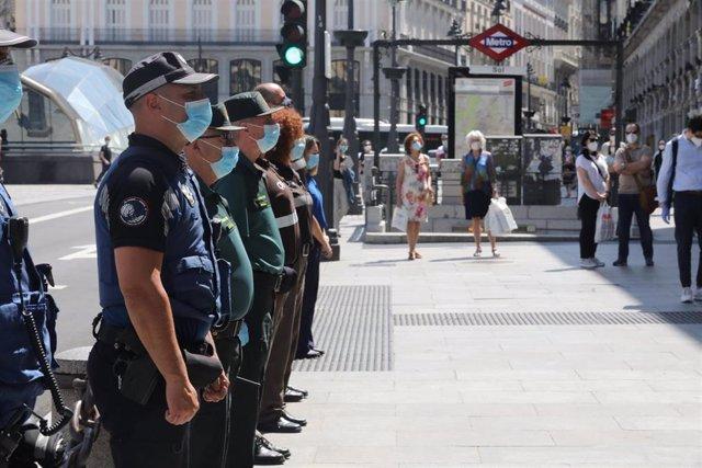 Miembros de distintos cuerpos de seguridad, como la Guardia Civil y la Policía Municipal de Madrid, guardan un minuto de silencio en memoria por los fallecidos por el COVID-19 en la Puerta de Sol.