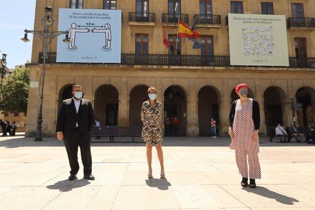El vicepresidente Javier Remírez, la presidenta María Chivite y la consejera de Salud, Santos Induráin, ante los mensajes de distancia de seguridad colgados en la fachada del Palacio de Navarra