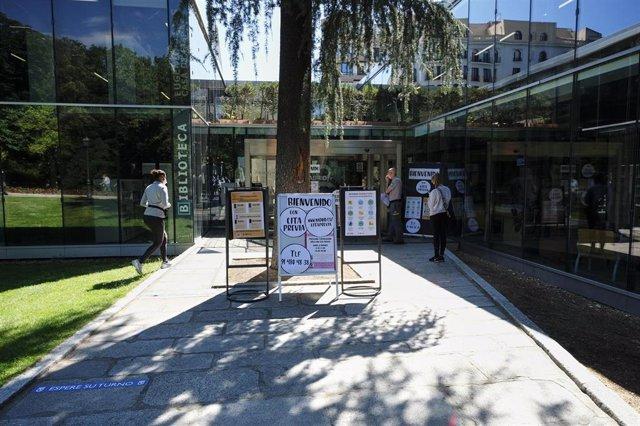 Transeúntes observan la puerta de la Biblioteca Pública Municipal Eugenio Trías