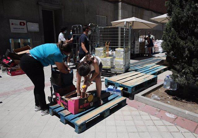 Una mujer recoge productos que le entrega una voluntaria a las puertas de la Parroquia Santa María Micaela. En Madrid (España), a 29 de mayo de 2020.