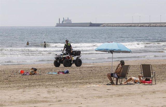 Un agente de la Policía Local de Valencia vigila desde un quad la Playa de la Malvarrosa.
