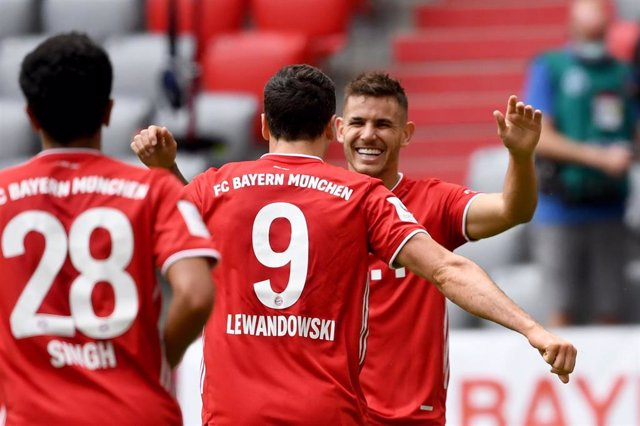 20 June 2020, Bavaria, Munich: Munich's Robert Lewandowski (C)celebrates scoring his side's third goal with his team mate Lucas Hernandez during the German Bundesliga soccer match between FC Bayern Munich and SC Freiburg in the Allianz Arena.