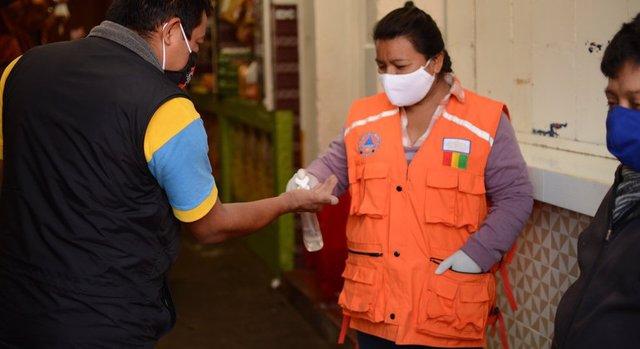 Una mujer aplica desinfectante de manos a un cliente a la entrada de un mercado municipal en la ciudad guatemalteca de San Marcos.