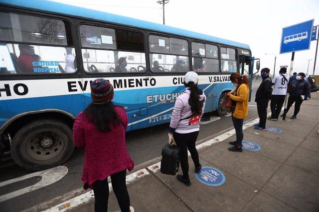 Un grupo de personas mantienen las distancias sociales mientras esperan en una parada de autobús de Lima, Perú.