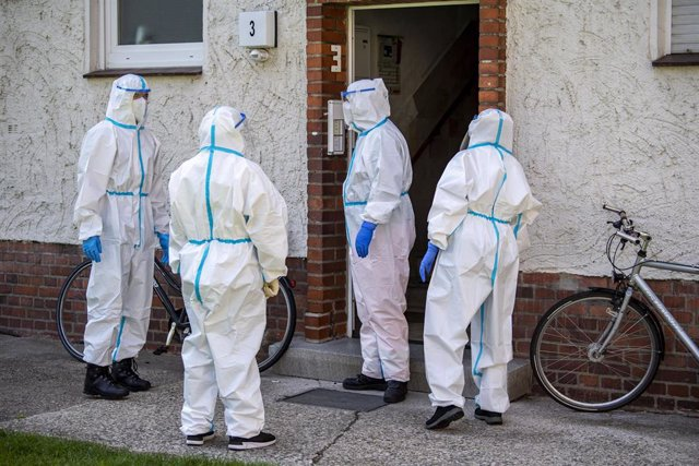 Voluntarios de Cruz Roja entran en un edificio de apartamentos para hacer pruebas de coronavirus