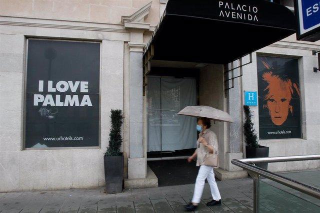 Una mujer pasa junto al exterior del Hotel Palacio Avenida, cerrado, durante el estado de alarma.