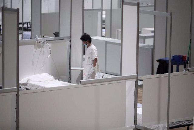 Un profesional sanitario frente a una cama vacía en el interior del hospital de campaña de IFEMA durante su último día de funcionamiento por la bajada de la presión asistencial. En Madrid (España) a 30 de abril de 2020.