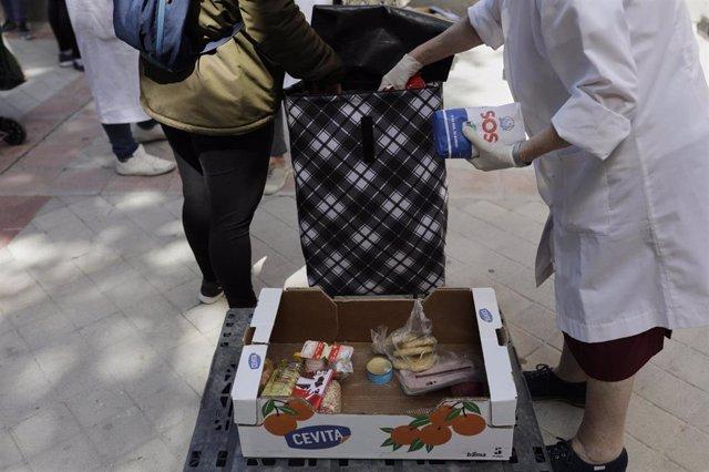Voluntarios de la Fundación Madrina, entidad que lleva 20 años trabajando para ayudar a madres en situación de exclusión y a sus bebés, reparten alimentos a las madres que esperan en las inmediaciones de la Parroquia Santa María Micaela y San Enrique.