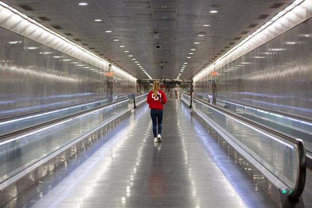 Una voluntaria de Cruz Roja camina por la estación catalana de Diagonal donde están repartiendo mascarillas con motivo de la reactivación de la actividad laboral no esencial en Cataluña en las empresas cuyos empleados no puedan teletrabajar, cuando se cum
