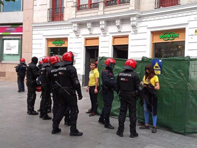 Ertzainas identifican a miembros de Ernai por obstaculizar la entrada a una sucursal de la Caixa en Bilbao.