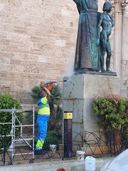 Un operario de Emaya limpia la pintada de la estatua de Juníper Serra en Palma.