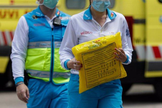 Dos sanitarios del SUMMA llevan un kit de material de protección para los compañeros.