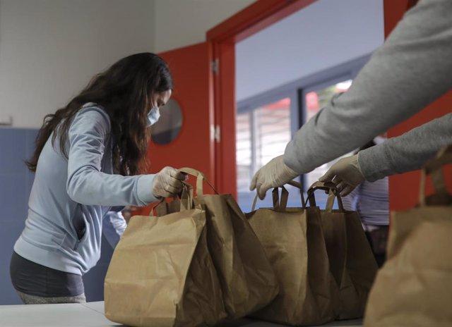 Una mujer atendida por una trabajadora de la Fundación Don Bosco recibe alimentos del Proyecto Fraternitas, que atiende a familias vulnerables de dos de los barrios más pobres de España, el Polígono Sur y Tres Mil Viviendas de Sevilla. Estado de alarma.