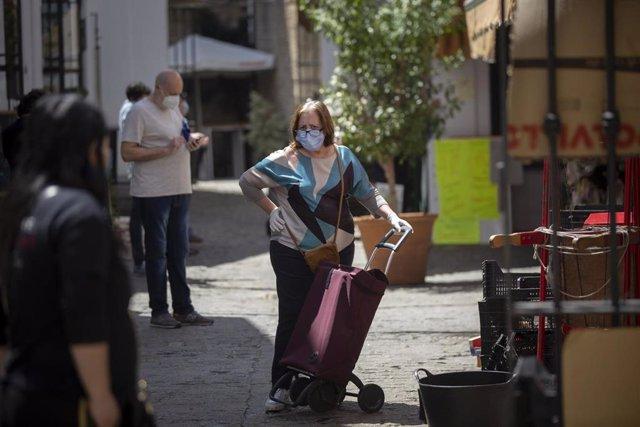 Una mujer protegida con mascarilla y guantes espera su turno en el Mercado de la Feria, un día después de que el Gobierno de España anunciara las medidas de desescalada por la pandemia del coronavirus, (Covid-19). En Sevilla, a 29 de abril de 2020.