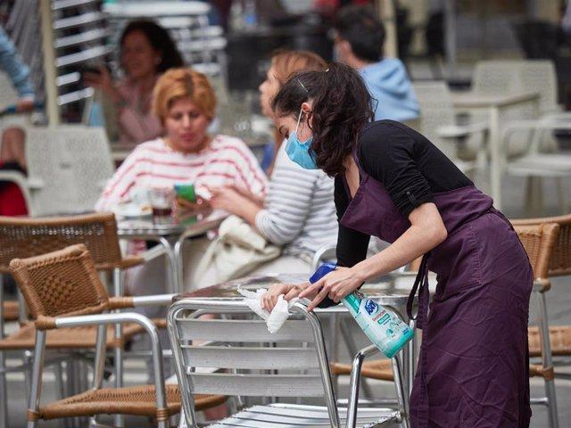 Una trabajadora desinfecta las mesas y sillas de una terraza