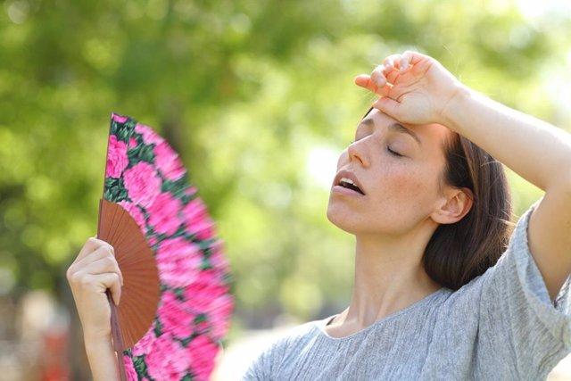 Mujer abanicándose en la calle con un abanico por las altas temperaturas y el calor de verano