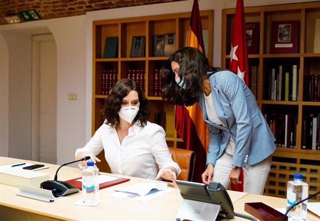 La presidenta de la Comunidad de Madrid, Isabel Díaz Ayuso (i), durante un Consejo de Gobierno Extraordinario.