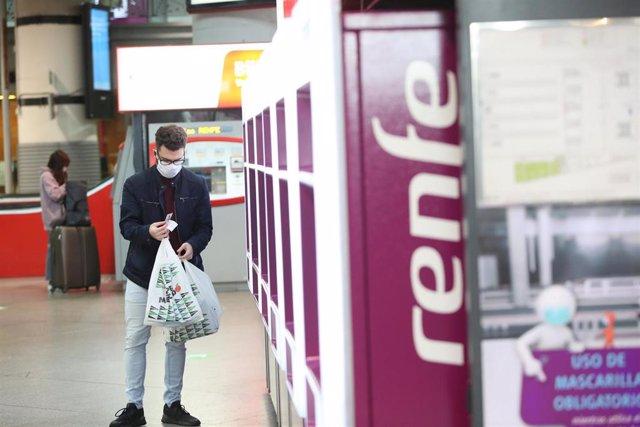Un viajero con mascarilla obtiene un billete en un dispensador en una estación