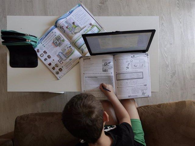 Un alumno de primaria hace los deberes de la asignatura de Inglés con varios libros y un ordenador, foto de archivo