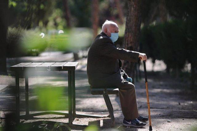 Un anciano con mascarilla descansa en el Parque Calero, en el distrito de Ciudad Lineal de la capital, uno de los que el Ayuntamiento de Madrid ha abierto y en los que se permite pasear y hacer ejercicio, en Madrid (España), a 8 de mayo de 20202.