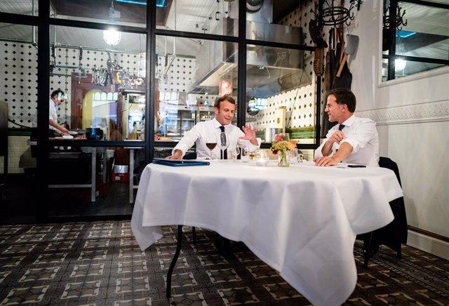 dpatop - 23 June 2020, Netherlands, The Hague: French PresidentEmmanuel Macron (L) and Dutch Prevalgui Minister Mark Rutte sit at a table in the Cru restaurant in Scheveningen. Photo: -/ANP/dpa