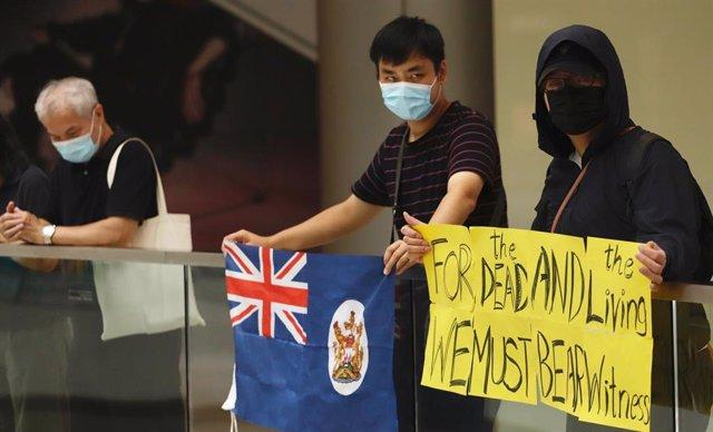 Manifestantes hongkoneses con una bandera de la época colonial.