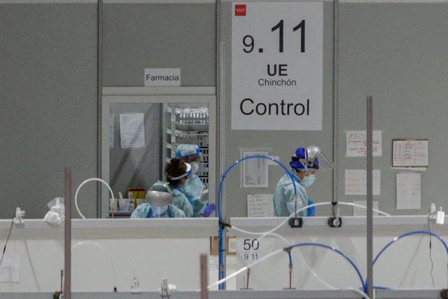 Sanitarios protegidos con mascarillas, gorros y pantallas protectoras en la puerta del almacén de material farmacéutico en el Hospital temporal de la Comunidad de Madrid habilitado en IFEMA para pacientes con coronavirus, en Madrid (España) a 31 de marzo