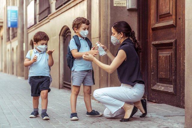 Uso de geles hidroalcohólicos  en niños. Madre con dos niños.