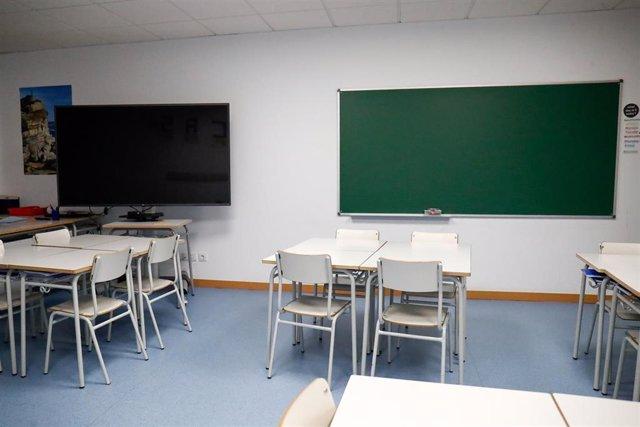 Sillas y mesas de un aula en el interior de un colegio.