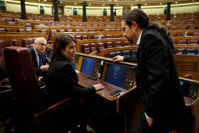 El vicepresidente segundo y ministro de Derechos Sociales, Pablo Iglesias conversa con la portavoz del grupo socialista, Adriana Lastra, durante el pleno celebrado este miércoles en el Congreso, donde el gobierno expone los resultados de los últimos conse